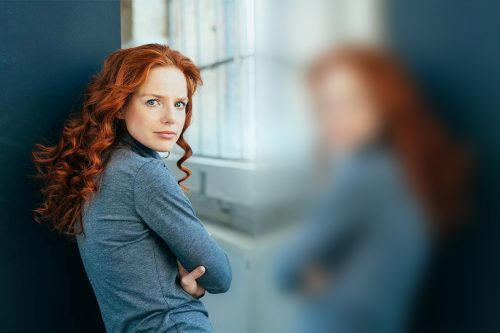 Thoughtful attractive redhead woman turning